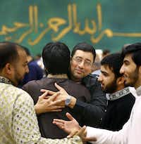 Raza Sayed (center) of Richardson greets friends Sunday after the prayer at the Dallas Convention Center. Thousands attended a sermon and prayer presented by the Islamic Association of North Texas at the convention center to celebrate the end of Ramadan.
