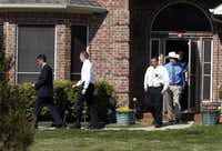 Law enforcement agents leave the home of Kaufman County District Attorney Mike McLelland and his wife, Cynthia, near Forney on Monday afternoon.
