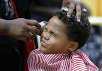 Tyshawn Jensen, 8, grimaced as Terra Jackson got close with the shears but the spiffy results no doubt were worth it( David Woo  - Staff Photographer)