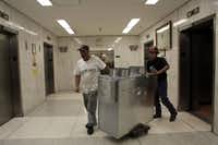 Dennis Jones (left) and Juan Montesinos roll the air distribution boxes hrough the halls. The new energy system will save $900,000 a year, the contractor says.