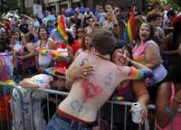Diana Estrada of Plano receives a free hug from a Alan Ross Texas Freedom Parade participant on Cedar Springs Rd. in Dallas, Sunday, September 21, 2014. The gay, lesbian, bisexual and transgender parade, which had over 80 entries, ended at Lee Park. (Tom Fox/The Dallas Morning News)(Tom Fox - Staff Photographer)