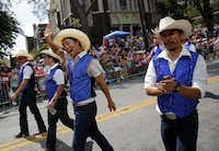 A group of dancing cowboys wave to crowd during the Alan Ross Texas Freedom Parade on Cedar Springs Rd. in Dallas, Sunday, September 21, 2014. The gay, lesbian, bisexual and transgender parade, which had over 80 entries, ended at Lee Park. (Tom Fox/The Dallas Morning News)(Tom Fox - Staff Photographer)