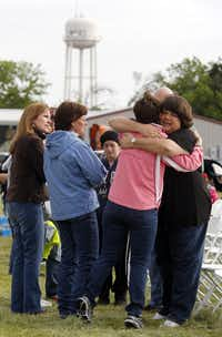 Sharon Middlebrook, center, gives a hug to the pastor's wife, Lisa Crowder, right,  prior to an outdoor service, on April 21, 2013, for the First Baptist Church of West, which was damaged by a fertilizer plant explosion. (Michael Ainsworth/The Dallas Morning News)(Michael Ainsworth - Staff Photographer)