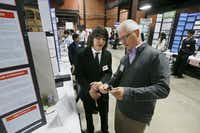 "Ayaz Hafiz, of Jasper High School of Plano, (left) shows Judge Ron Johnson, a part of a speaker, while discussing his project, ""Improving The Efficiency of CNT Thermo Acoustic Speakers"" during the annual Dallas Science Fair is held at Fair Park, in Dallas on Feb 21, 2015. (Michael Ainsworth/The Dallas Morning News)(Michael Ainsworth - Staff Photographer)"