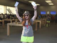 Jill Cain, who waited in line 49 hours, ecstatically leaves the Apple Store on Knox Street with two iPhones.