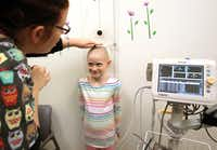 Nichole Cook (left) checks Libby Serber's height at Children's Medical Center in Plano.