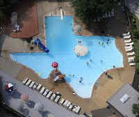 Swimmers enjoy The Texas Pool, a pool shaped like the state of Texas, located at 901 Springbrook Dr. in Plano, Texas. Two swimmers leap from a platform in the center of the pool on a very hot summer day Friday, June 22, 2012.