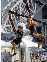 Landon Moninger, 13, and his sister Sage Moninger, 11, enjoy the zip line near the Kid Zone at Cowboys Stadium on Sunday September 23, 2012.