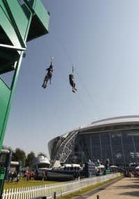 People take advantage of a zip line near the Kid Zone at Cowboys Stadium on Sunday September 23, 2012.