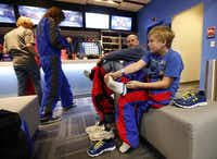 IAN GETS DRESSED  after a skydive with his father, Greg Adams. First-time fliers can enter the wind tunnel for about $60.Tom Fox - Staff Photographer