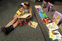 Jill Creel reads with 2-year-old son Hunt Creel at a workshop at the Park Forest Branch Library in Dallas.