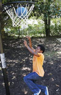 David Williams, 12, takes a five-minute break from his home schooling to shoot some hoops in his back yard.