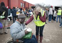 Kelly Ann Scott, a volunteer, gave Bob Johnson a wrapped plate of food to go with his gifts during the outdoor celebration that drew about 250 diners.