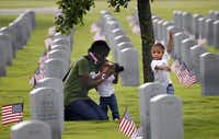 Brandy Baxter enjoyed a moment with her two daughters Faith, 2, (left) and Joy, 3, while their family visited the D-FW National Cemetery to place flags on Sunday. Brandy Baxter and her husband, Herman Baxter, are both Air Force veterans and now members of Iraq and Afghanistan Veterans of America.