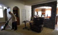 Kenneth Robinson vacuums the spacious living room of the Flower Mound home he's occupying.