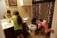 Mia Soto, 6, left, and Mya Soto, 6, checked their bathroom sink and toilet on Thursday to see if the water has been turned back on at their home in Anna. A water main was hit by a construction crew while relocating water and sewer lines for road construction. Residents are advised to boil their water before drinking.