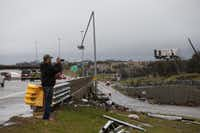 An onlooker takes pictures of the damage after a tornado hit last night in Garland, Texas on December 27, 2015. (Nathan Hunsinger The Dallas Morning News)