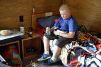 "Payton Stewart, 9, who lost his father to a heart attack, cools off with a fan during quiet time in his cabin at Camp El Tesoro de la Vida, ""the treasure of life.""( Lara Solt  -  Staff Photographer )"