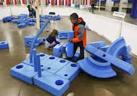 Ava Meyers, 5, and Noah Cypull, 8, play in the Imagination Playground at Fair Park. Friday's Day 1 Festival will include activities built around New Year's resolutions — for instance, eating healthy, exercising more or traveling to new places.( David Woo  - Staff Photographer)