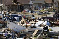 A volunteer (right) takes a break from cleaning away debris from a tornado ravaged home on Oceanport Dr. and Bayport Dr. in Garland, Texas, Wednesday, December 30, 2015. An EF-4 tornado, which tore a path through the community south of Interstate 30 and the George Bush Tollroad (Tom Fox/The Dallas Morning News)