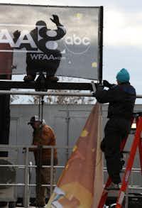 Jonathan Jones (top), David Hope (right) and Dwayne Buchanan hang up signs for the Big D NYE celebration at Victory Plaza.