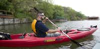 Marine veteran Sam More moves his kayak to another location after fishing near a pier on Moss Lake near Gainsville.