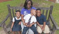 Latoya Cooper (center) lost her husband to complications from diabetes recently. Her daughter, Trinity (left), 5, and nephew Johnathan Bryant (right), 7, attend classes at Sam's Place, a grief counseling service provided by the Grief & Loss Center of North Texas. Her son, Steven, 2, center, is too young to participate.( Photos by Rex C. Curry  - special contributor)