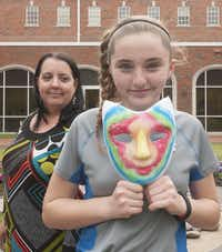Raine Cockrell holds a mask painted on the outside to represent how she presents herself to the world and painted on the inside to represent how she really feels. Her father died recently. Her mother, Kelly, is at left.(Rex C. Curry - Special Contributor)