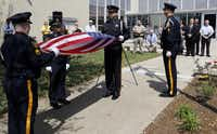 Dallas County Sheriff's Department Honor Guard members fold the U.S. Honor Flag that was flown for 24 hours over the Kaufman County Courthouse in downtown Kaufman.  The flag was raised Monday in memory of Mike and Cynthia McLelland and Mark Hasse.