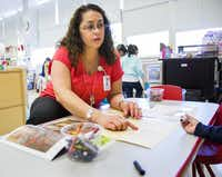 Pre-K Specialist Yvette Delgado works with prekindergarten students on Thursday at Gill Elementary School in Dallas.( Ashley Landis  -  Staff Photographer )