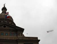 """A single-engine airplane with a sign that reads """"God Bless Texas"""" circles overhead during the inauguration."""