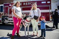 Chloe Mallory (left) with Candice Mallory and 3-year-old Hank Mallory, attended Monday's commemoration of the Paris fire with Sam the dog, who played the role of a fire dog.( Ashley Landis  -  Staff Photographer )