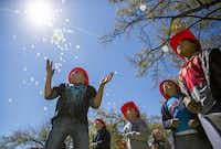 """Second-graders set balloons aloft that bore the message """"SMILE"""" at Monday's centennial commemoration of the Paris fire. """"SMILE"""" became a mantra for residents in the days after the fire.( Ashley Landis  -  Staff Photographer )"""