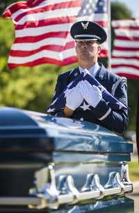 A member of a military honor guard holds a folded American flag over the remains of retired Army Air Corps 1st Lieutenant Calvin Spann during funeral services  on Saturday, September 12, 2015 at Covenant Church in Carrollton, Texas.  Spann was an original Tuskegee Airman and fighter pilot with the 100th Fighter Squadron of the 332nd Fighter Group.  He served during World War II, when he flew 26 combat missions. (Ashley Landis/The Dallas Morning News)(Ashley Landis - Staff Photographer)