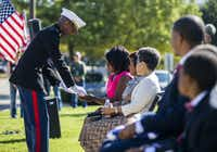 U.S. Marine Major Alejandro House, retired, presents Dr. Carla Spann Lopez with shells from a nine-gun salute during funeral services for her father, retired Army Air Corps 1st Lieutenant Calvin Spann, on Saturday, September 12, 2015 at Covenant Church in Carrollton, Texas.  Spann was an original Tuskegee Airman and fighter pilot with the 100th Fighter Squadron of the 332nd Fighter Group.  He served during World War II, when he flew 26 combat missions. (Ashley Landis/The Dallas Morning News)(Ashley Landis - Staff Photographer)