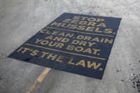 A sign painted on a boat ramp at Arrowhead Park urges boaters at Lewisville Lake to do their part to rein in the spread of zebra mussels.