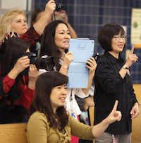 Fang Wang, standing, Gloria Teng, sitting, and Bee Ong, right, help lead the students  in song as part of Weaver's  anniversary celebration in Garland.( Staff photo by LOUIS DELUCA   -  DMN )