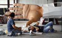 SRO scenic artist Amy Martin applied a coat of special silicone paint to Big Tex's left hand on Sept. 9. Helping out was the Boerne company's lead scenic artist, Dina Zavala.