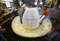 A big head requires a big hat -- Tex's weighs a whopping 900 pounds even though it's made largely of Styrofoam. Assembly was done in July by SRO workers including fabricator Cameron Beesly (left) and scenic artists John Godwin and Mike Lindon.