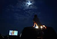A young visitor climbs to the roof a a pick up truck for a better view at The Brazos Drive-In Theatre in Granbury, Texas. The drive-in movie house is back in business after a May storm destroyed part of the screen and the roof above the projector.( DAMON WINTER  - 172812)