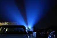A moviegoer gets comfortable with his feet hanging out of his truck window during the show. The Brazos Drive-In Theatre is back in business after a May storm destroyed part of the screen and the roof above the projector.( DAMON WINTER  - 172812)
