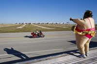 """A ballerina fat suit fit the occasion for this NASCAR fan who waved to motorists Friday outside a campground at Texas Motor Speedway. """"We're just salt-of-the-earth, down-home people out here,"""" another fan said."""