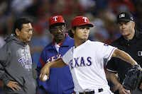Yu Darvish's interpreter (left) bridged the language gap between the Japanese starting pitcher and Texas Rangers manager Ron Washington and umpire Gary Darling.(File 2012 - Staff Photo)