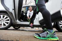 Angie Barrientos helped her husband, Alex, by tying his shoes along an adapted route run by marathoners on Sunday.