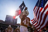 University of Texas tight end Logan Mills carried the Texas flag as he led the team onto the field before the 2015 Red River Showdown. (2015 File Photo/Smiley N. Pool)