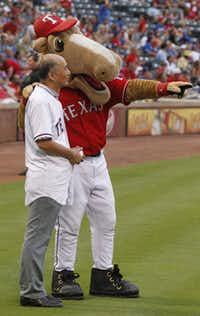 "Japanese Ambassador Kenichiro Sasae get a pointer from Texas Rangers mascot ""Champ"" as he prepared to throw out a ceremonial pitch during their MLB baseball game at Rangers Ballpark in Arlington on Wednesday."