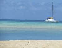 A single sailboat glides past an uninhabited motu in the Tuamotu Archipelago in French Polynesia.