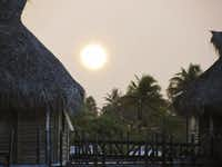 Post-tropical storm sun sets over Tikehau Pearl Beach Resort, a small collection of over-the-water bungalows that stays true to the South Pacific aesthetic of woven niau, teak, kohu and coconut.