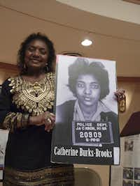 Catherine Burks-Brooks holds a poster of her mug shot, taken after her arrest in Jackson, Miss., during the Freedom Rides. She was speaking at the Birmingham Civil Rights Institute.