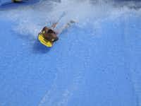 Bodyboarding on the Boogie Bahn wave simulator at Schlitterbahn Galveston Island Waterpark. At the attraction, water surges at 50,000 gallons per minute up a wave shape, simulating an ocean breaker. The water layer is about an inch deep, enough for riders trying their skills.Mary Ellen Botter